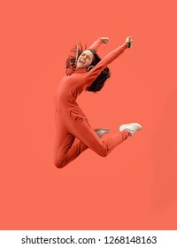 Freedom in moving. Mid-air shot of pretty happy young woman jumping and gesturing against coral studio background. Runnin girl in motion or movement. Human emotions and facial expressions concept