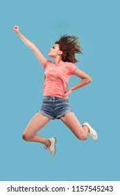 Freedom in moving. move only forward. pretty happy young woman jumping and gesturing against blue studio background. Runnin girl in motion or movement. Human emotions and facial expressions concept