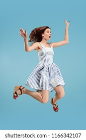 Freedom in moving. Surprised, pretty, happy young woman jumping and gesturing against blue studio background. Runnin girl in motion or movement. Human emotions and facial expressions concept