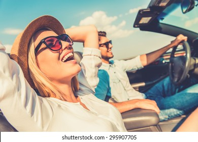 Freedom of the open road. Side view of joyful young woman relaxing on the front seat while her boyfriend sitting near and driving their convertible