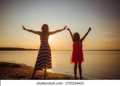 Freedom people living a free, happy, carefree life at beach. Silhouettes of mom and daughter at sunset arms raised up showing happiness and a healthy lifestyle against a colorful sky background.