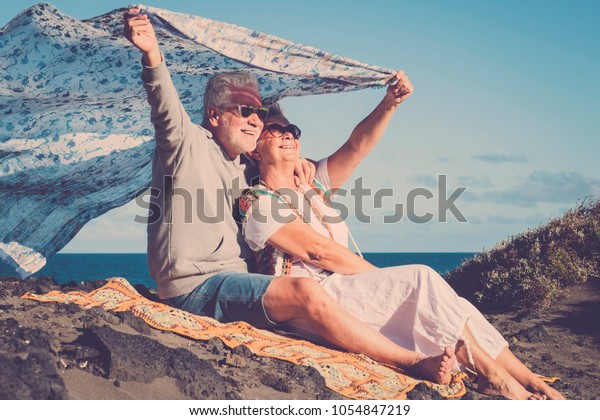 freedom and rebel hippies man and woman senior aged 70 years old. rest at the beach and enjoy freedom and the good weather.