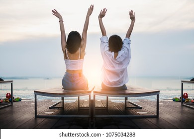 freedom and relax with two asian girl hand up look to sunset near beach swimming pool with happiness moment