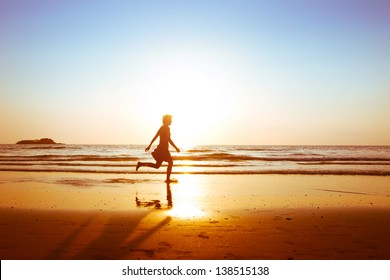 freedom, silhouette of young happy carefree girl running on the beach at sunset