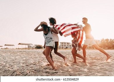Freedom is in their veins. Cheerful young people carrying American flag while running along the beach together