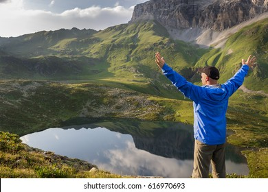 Freedom traveler man standing with raised arms and enjoying a beautiful nature