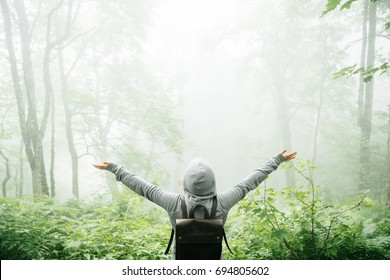 Freedom traveler stood with his arms raised and enjoying the beautiful nature with fog.