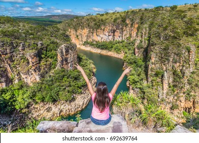 Freedom traveler woman with raised arms on the top of Furnas Canyon enjoying the beautiful landscape. Concept of travel and freedom. Capitolio, Minas Gerais, Brazil.