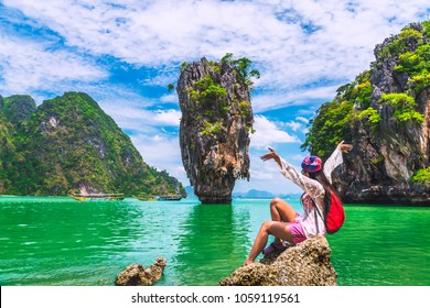 Freedom traveler woman relaxing on rock joy view of James Bond island, Phang Nga bay, near Phuket, Adventure nature travel in Thailand, Beautiful destination landscape place Asia, Summer vacation trip