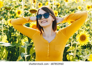 Freedom and wellbeing concept. Summer girl on sunglasses. Beautiful cheerful young woman with sunflower enjoying nature and laughing on summer sun flower field. Sunflare, sunbeams, glow sun. Backlight