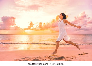 Freedom wellness well-being happiness concept. Happy carefree Asian woman feeling blissful jumping of joy on peaceful beach at sunset. Serenity, relaxation, mindfulness, stress free concepts.