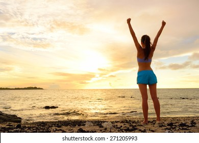 Freedom winning woman cheering at sunset beach. Success concept with female adult from the back arms up at the sky looking at the ocean feeling free and successful. Achievement of her life.
