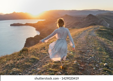 Freedom woman in free happiness bliss open arms at mountain peak. Happy female model in summer dress enjoying serene ocean nature during. Freedom and healthy concept.