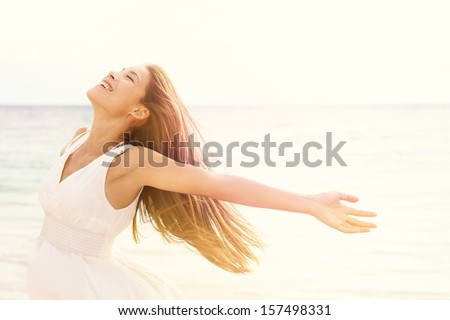 Freedom woman in free happiness bliss on beach. Smiling happy multicultural female model in white summer dress enjoying serene ocean nature during travel holidays vacation outdoors.
