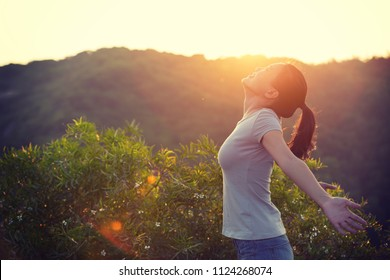 freedom woman raised arms to sunrise on mountain top in the moring