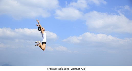 freedom young asian woman jumping against blue sky