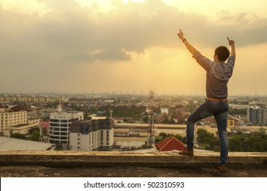 freedom Young Man with Hands Up on the city sunset Background