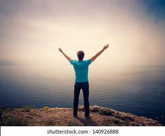 freedom. a young man standing on a hill with raised hands