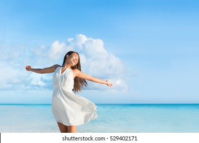 Freedom young woman with arms up outstretched to the sky with blue ocean landscape beach background copy space. Asian girl in white dress dancing carefree in sunset.