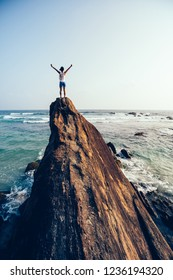 Freedom young woman outstretched arms on seaside rock cliff edge