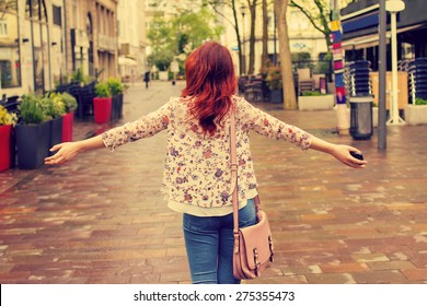 Freedom-Young woman with raised hands in a city.Young woman walking with raised hands feeling free.Life style