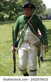 Freehold, New Jersey / USA - June 22, 2019: Revolutionary War reenactors wearing the green and white uniforms of the Loyalist 4th battalion of New Jersey at the Monmouth Battlefield State Park.