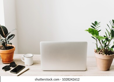 Freelance concept. Desktop with laptop, phone, notebook, coffee cup and plant. business workspace in home or office with work tools on wooden table. stylish work place