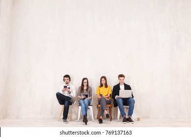 Freelance concept. Four young creative people work with gadgets sitting on chairs in large beautiful office - studio for co-working and outsourcing workers copyspace