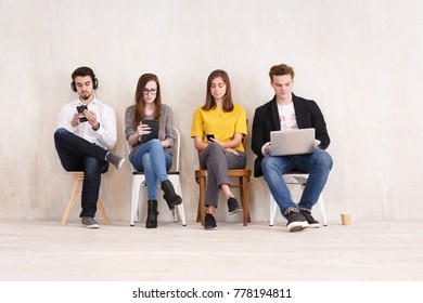 Freelance concept. Four young creative people work with gadgets sitting on chairs in large beautiful office - studio for co-working and outsourcing workers