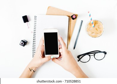 Freelance feminine workspace in flat lay style with smartphone in female hands, latte ice, notebook, spectacles, nail polish and lipstick. Top view