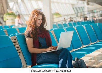 Freelance girl working, using her laptop while waiting for her flight in the international airport terminal. Modern job and distant education concept.