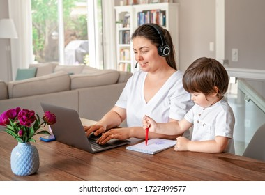 Freelance, online work, studying, learning with child concept. Home office. Woman with headphones working remotely on laptop while her little son drawing next to her.
