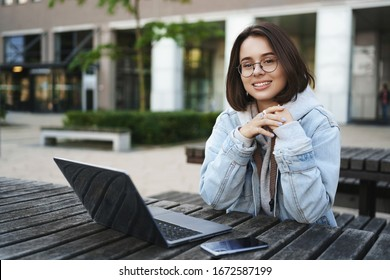 Freelance, people and education concept. Cheerful young attractive girl sitting alone on park bench, university, working remote with laptop, mobile phone, look away with pleased smile
