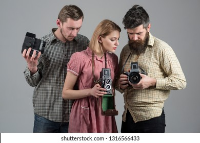 Freelance photographers. Paparazzi or photojournalists with vintage old cameras. Group of people with retro cameras. Photography studio. Retro style woman and men hold analog photo cameras.