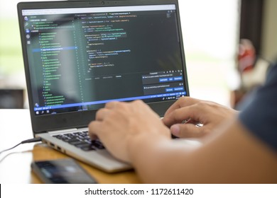 Freelance programmer or developer working at home and typing source code with laptop