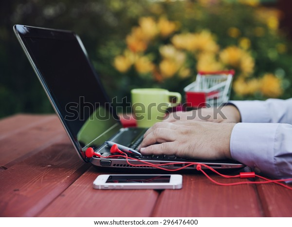 Freelance or remote work concept - male is using laptop computer.