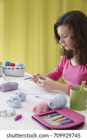 freelance woman creating handmade knit clothes at her studio