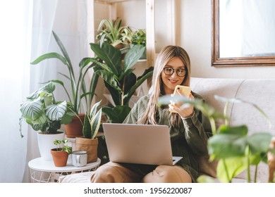 Freelance woman in glasses with mobile phone typing at laptop and working from home office. Happy girl sitting on couch in living room with plants. Distance learning online education and work.