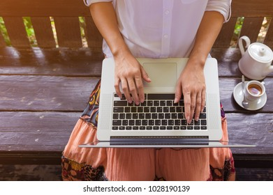 Freelance woman's hands on the keyboard laptop computer in a cafe, girl using laptop typing, web searching, browsing / soft focus image.