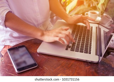 Freelance woman's hands on the keyboard laptop computer in a cafe with smartphone, girl using laptop typing, web searching, browsing / soft focus image.