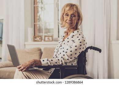 Freelance work. Amazing differently abled woman keeping smile on face while holding laptop on knees