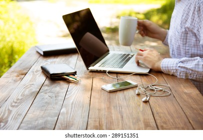 Freelance work. Casual dressed man sitting at wooden desk inside garden working on computer pointing with color pen drinking coffee gadgets dropped around on table side view