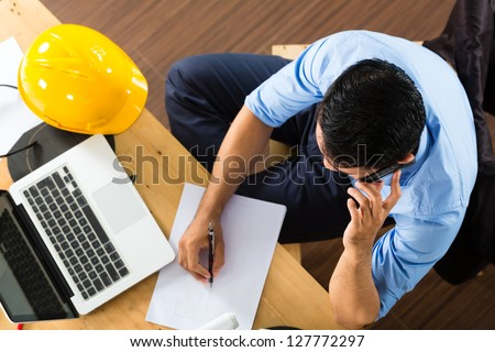 Freelancer - Architect working at home on a design or draft, on his desk are books, a laptop and a helmet or hard hat