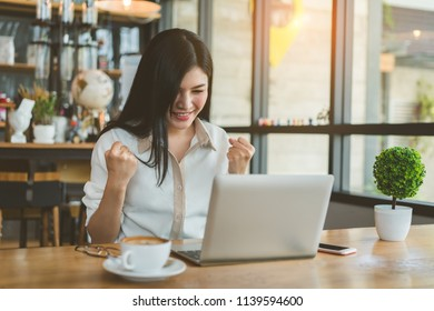Freelancer beautiful asian woman success business project with digital laptop computer happy and relax at workplace coffee shop in the evening near windows.