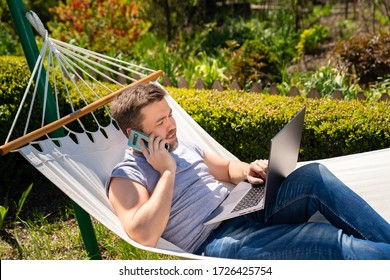freelancer businessman man lies in the hammock and working on the computer, answering a phone call. Remote working, isolation in quarantine. the social distance.