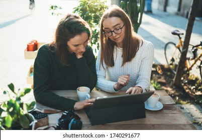 Freelancer communicate on project, girls drink coffee,  friends shopping online on wifi tablet in cafe outdoor. Students studies on internet. Working business process concept