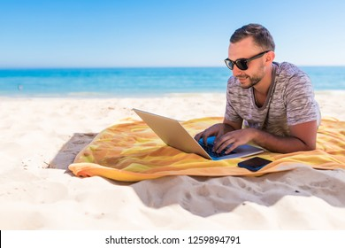 freelancer, happy successful businessman with laptop on the beach, blue sky