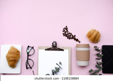 Freelancer home office desk workspace with blanket and stationery. Morning breakfast with coffee and croissant on pink background. Flat lay, top view still life concept.