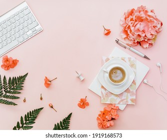 Freelancer home office desk workspace with keyboard and coffee cup on pink background. Flat lay, top view still life concept
