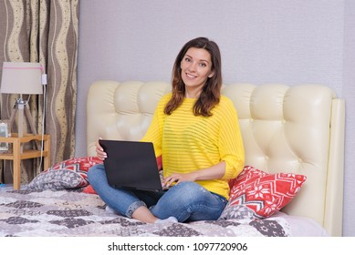 I'm a freelancer and I love working at home. Portrait of beautiful freelancer girl brunette in room on bed working on laptop. She sits right in front of the camera smiling and looks happy
